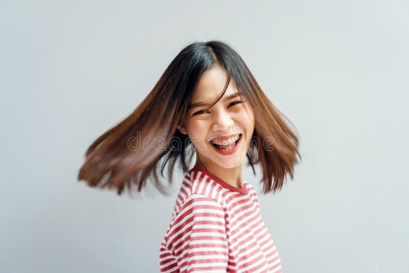 女孩愉快微笑和快乐在振翼沿转动的力量的一根打旋的姿态和头发的红色礼服 免版税库存图片