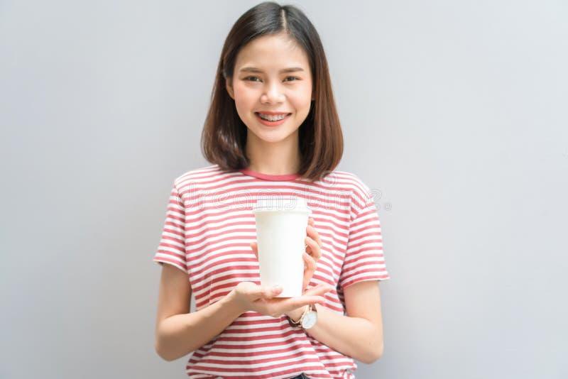 女孩愉快微笑和快乐在红色礼服举行一个加奶咖啡杯子在手中 库存照片
