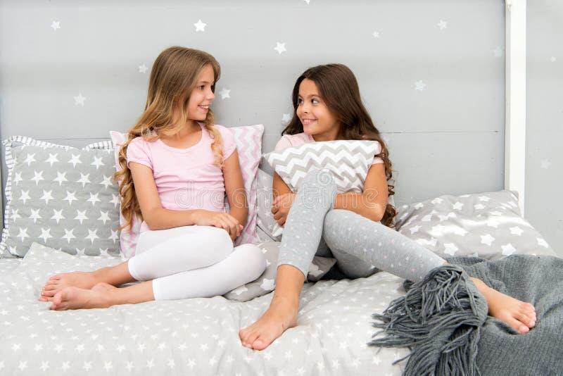 女孩愉快的最好的朋友或兄弟姐妹逗人喜爱的时髦的睡衣的有枕头sleepover党的 有的姐妹乐趣sleepover 免版税库存图片