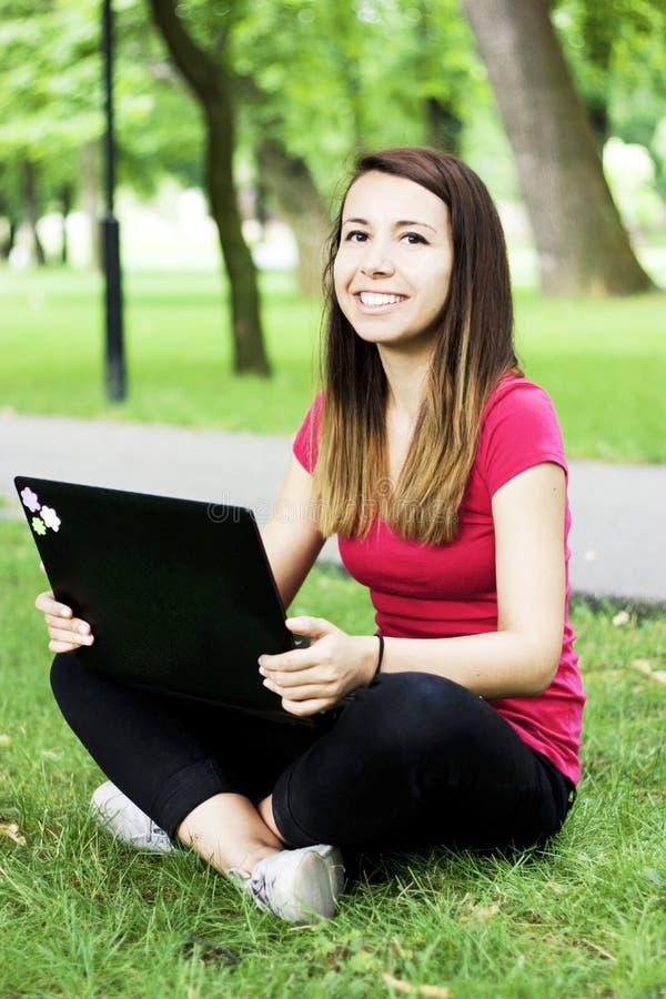女孩愉快的膝上型计算机 免版税图库摄影