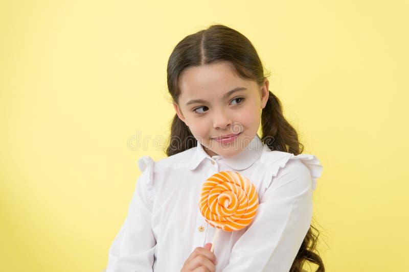 女孩愉快的面孔举行甜棒棒糖ok姿态 她该当了糖果 女孩喜欢甜糖果黄色背景 库存照片