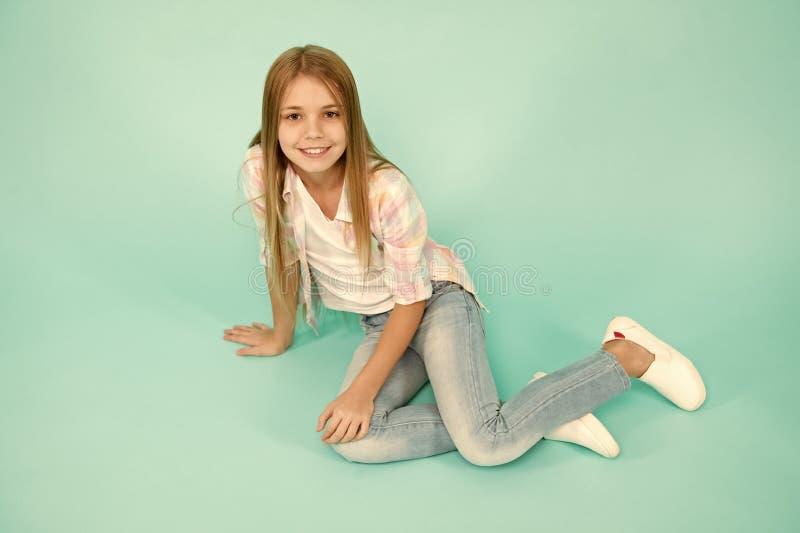 女孩愉快的面孔坐地板殷勤看的照相机绿松石背景 有长发放松的孩子女孩 expertize 免版税库存照片