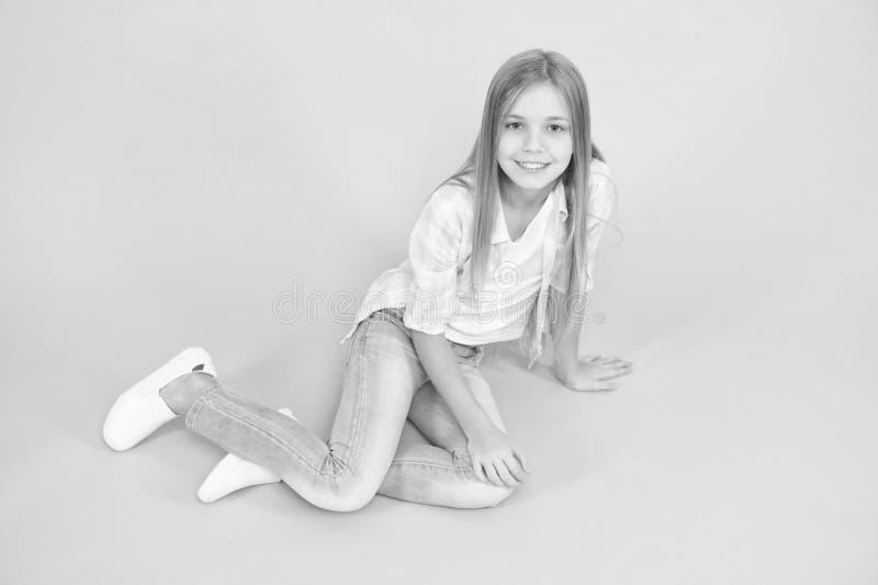 女孩愉快的面孔坐地板殷勤看的照相机绿松石背景 有长发放松的孩子女孩 expertize 免版税库存图片