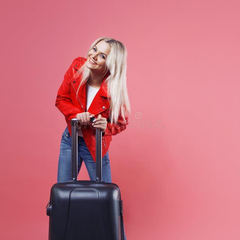 女孩愉快笑 带着手提箱的年轻美丽的白肤金发的妇女在桃红色背景 图库摄影