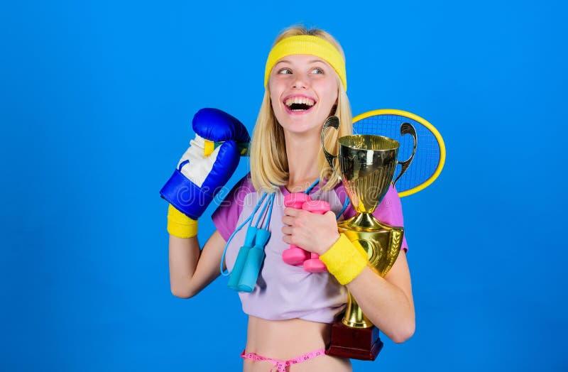 女孩成功的现代妇女举行金黄觚体育冠军和设备蓝色背景 如何发现时刻为 免版税库存图片