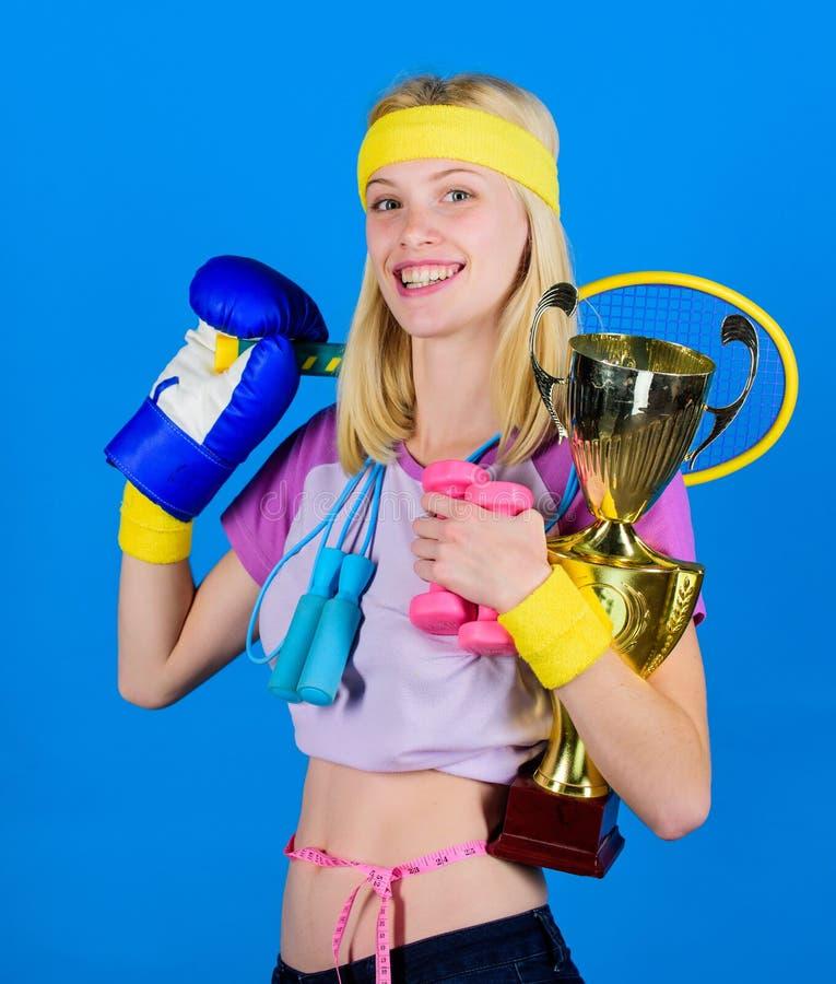 女孩成功的现代妇女举行金黄觚冠军 妇女好在网球跳跃的拳击健身体育 怎么 免版税库存图片