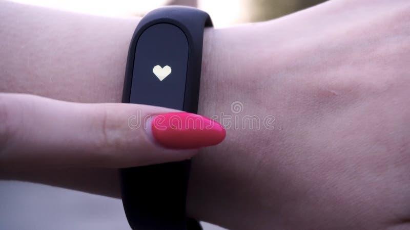 女孩戴着健身镯子 女孩检查在健身镯子或活动跟踪仪计步器的脉冲在腕子,体育 库存照片