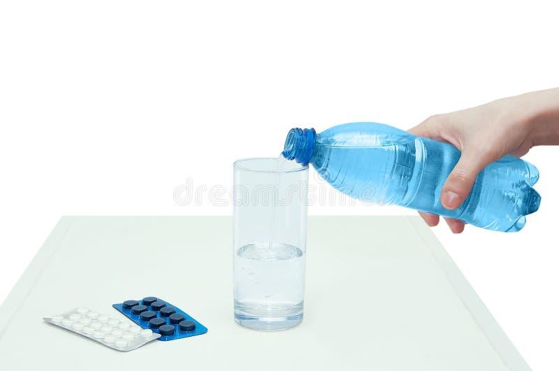 女孩手倾吐从瓶的水入玻璃 附近说谎包装与片剂 免版税库存图片