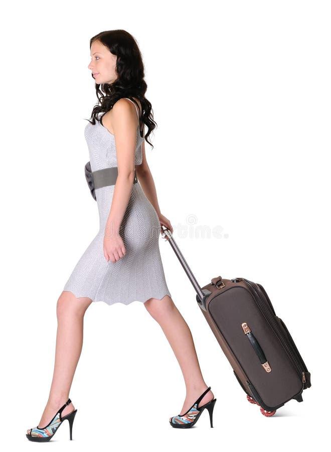 女孩手提箱走年轻人 库存照片