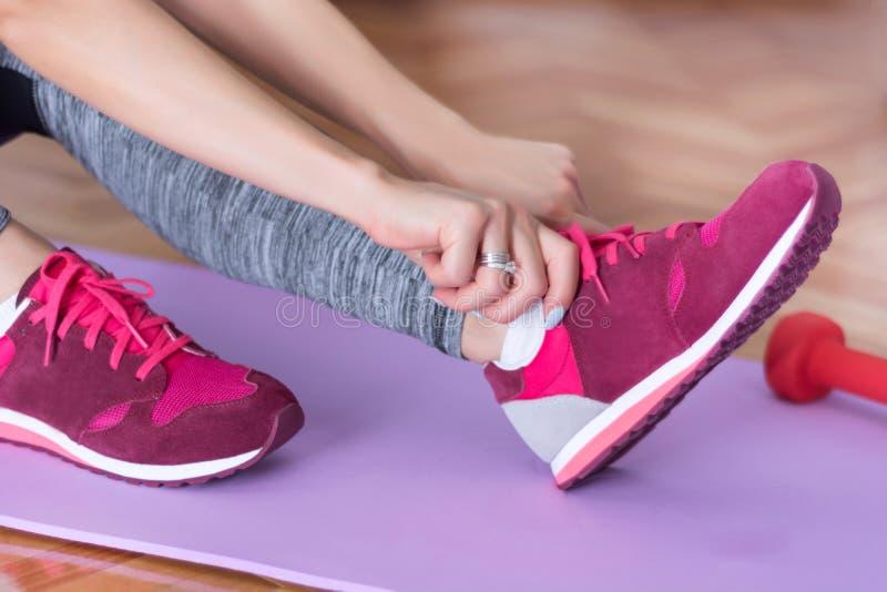 女孩手红色运动鞋为做准备在紫色瑜伽或健身席子在家解决 免版税库存照片