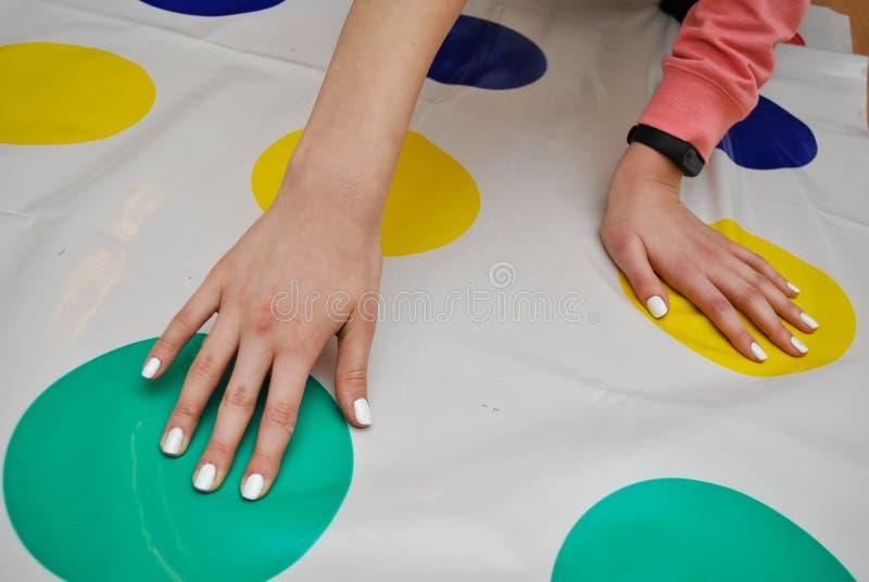 女孩打在地板上的转弯比赛,在五颜六色的圈子的手 在children& x27的趋向; s注意的反重音玩具 库存图片