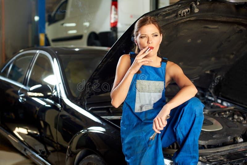 女孩技工在一辆汽车的敞篷抽烟在汽车服务的 免版税库存照片