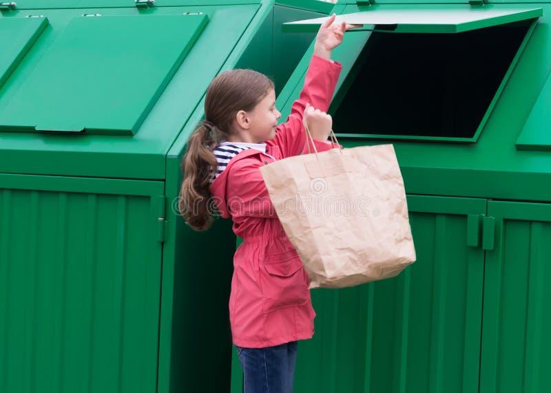 女孩把打开垃圾容器的一个纸袋扔出去 免版税库存照片