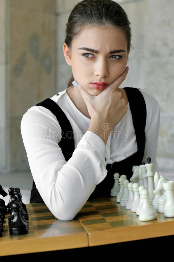 女孩投入了她的手对她的面颊在下棋比赛前 库存照片