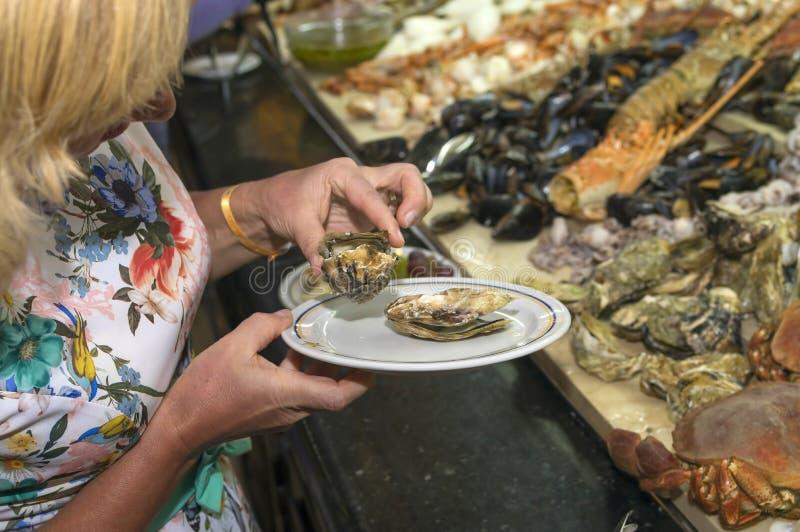 女孩投入淡菜板材,在一有名望的restau的晚餐 免版税库存图片