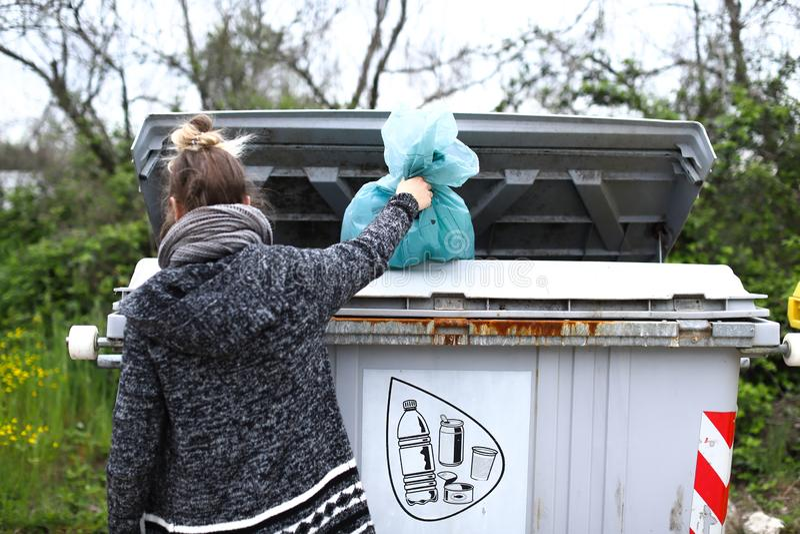 女孩投掷与塑料的袋子入垃圾箱 免版税库存照片