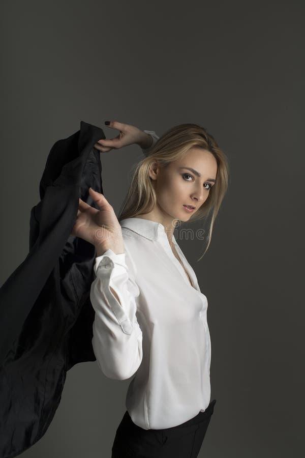 女孩投掷在她的肩膀的一件夹克 企业画象 免版税库存照片