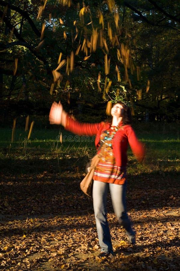 女孩投掷的秋叶 图库摄影