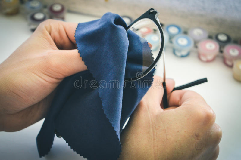 女孩抹玻璃与餐巾 免版税库存图片