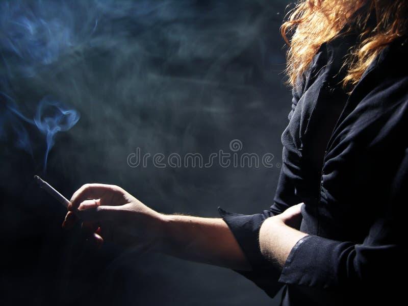女孩抽烟的年轻人 库存照片