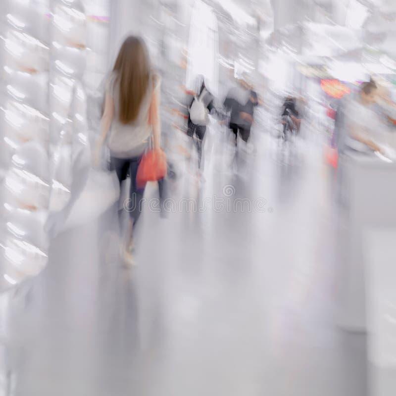 女孩抽象图有红色袋子特写镜头的,背景 Defocused行动弄脏了走在购物的青年人 库存图片