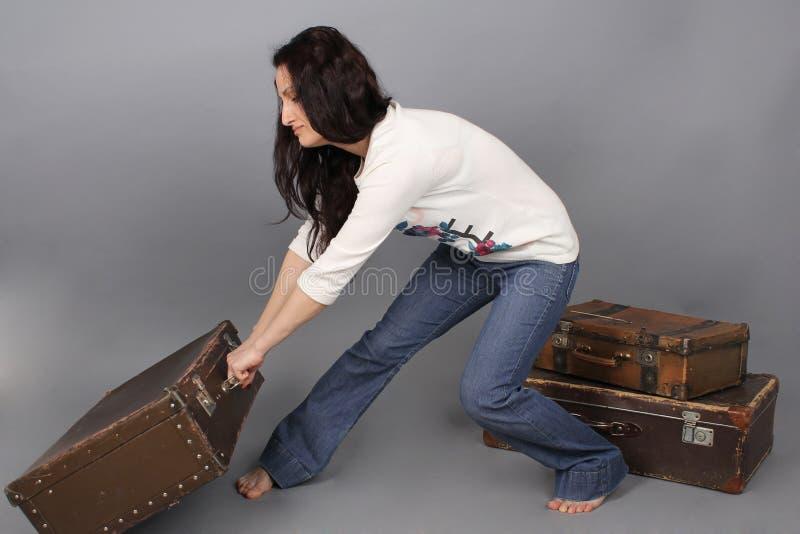 女孩拉扯一个巨大的手提箱 免版税图库摄影