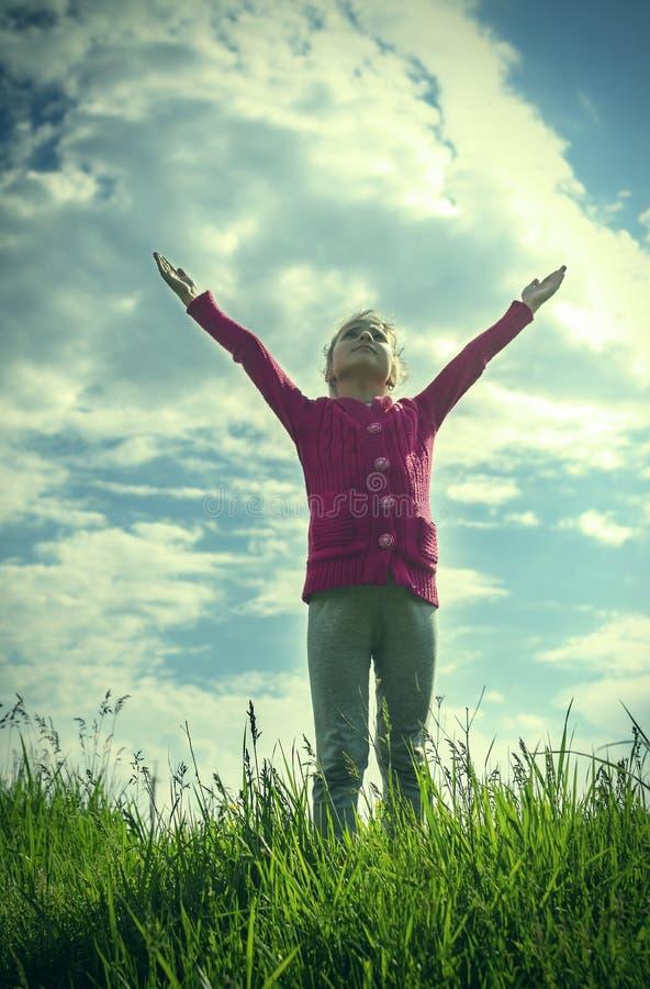 女孩拉扯手对天空。 免版税库存照片