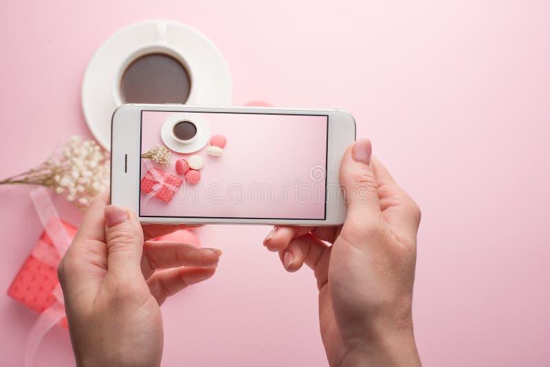 女孩拍在一个电话的照片在咖啡和蛋白杏仁饼干桃红色背景,instagram的 免版税库存图片