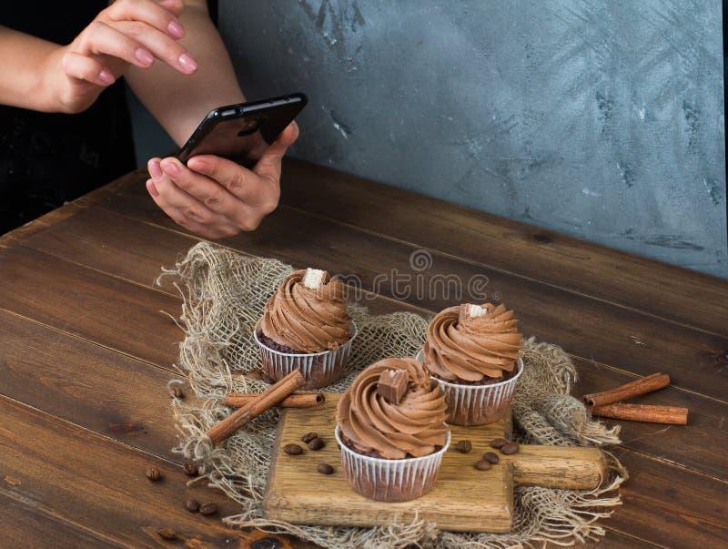 女孩拍摄智能手机说谎在一张木桌上的桂香巧克力杯形蛋糕和棍子 库存图片