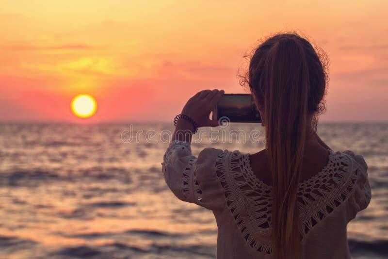 女孩拍日落的照片 免版税库存图片