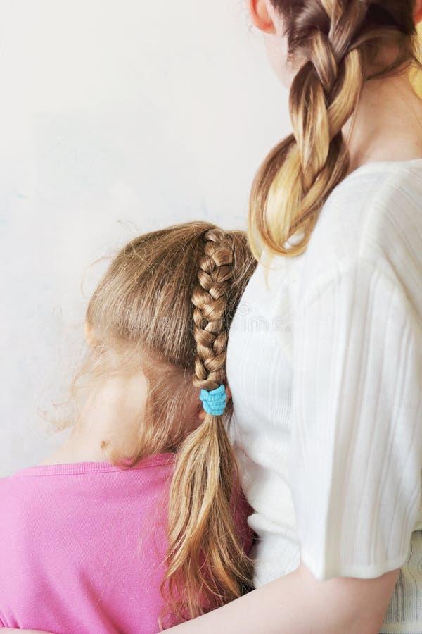 女孩拥抱有一条长的猪尾的一个小女孩 库存照片