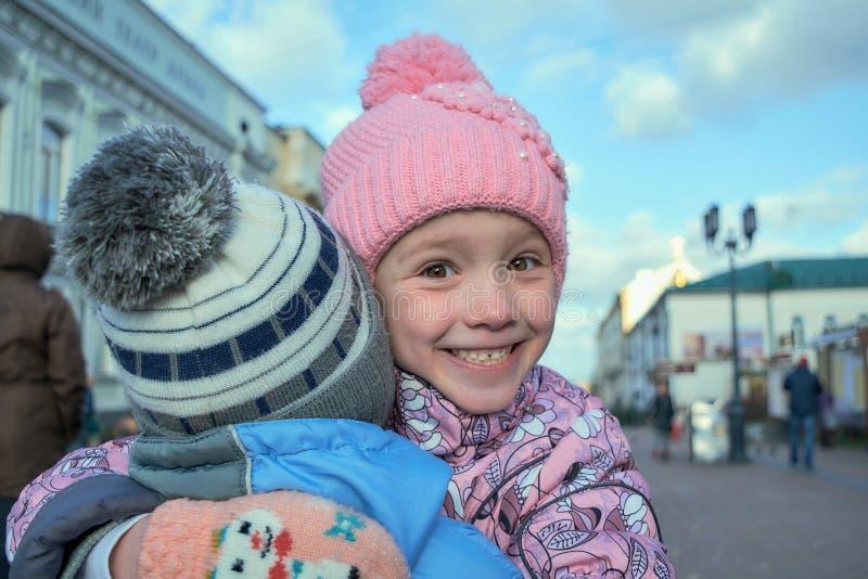 女孩拥抱男孩和微笑并且是愉快的 图库摄影