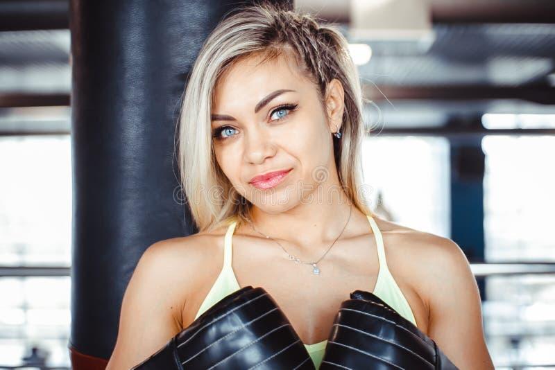 女孩拳击手打沙袋 库存照片