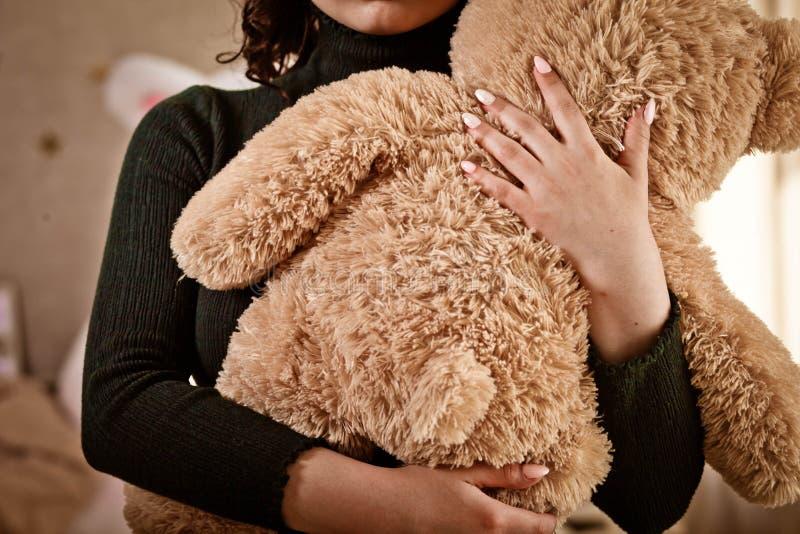 女孩拿着一个一玩具熊,女用连杉衬裤 免版税库存图片