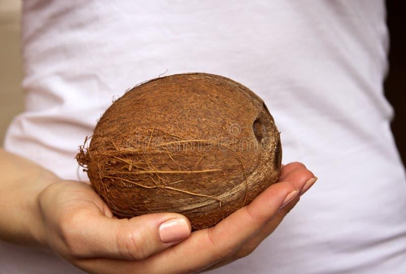 女孩拿着一个椰子 免版税库存图片