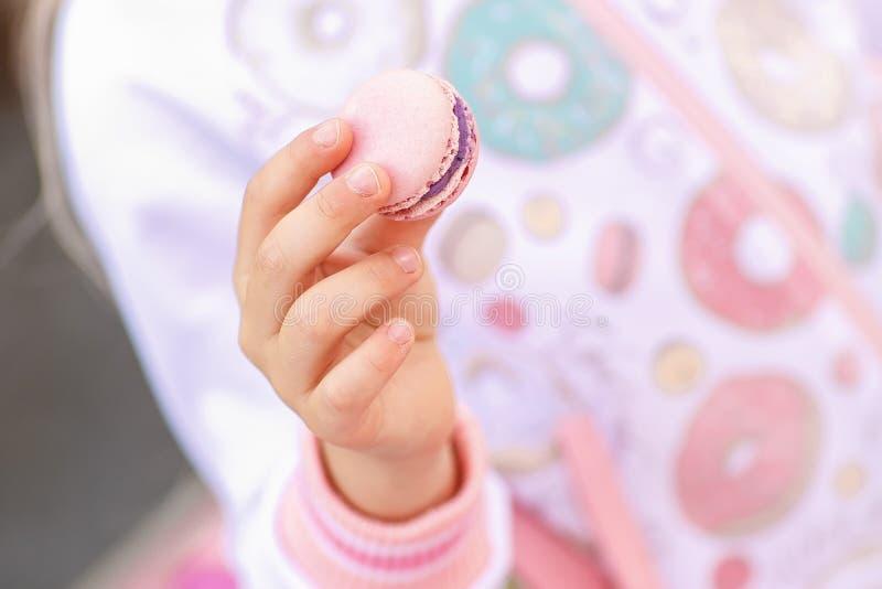 女孩拿着一个美丽的法国macarons蛋糕 免版税库存图片