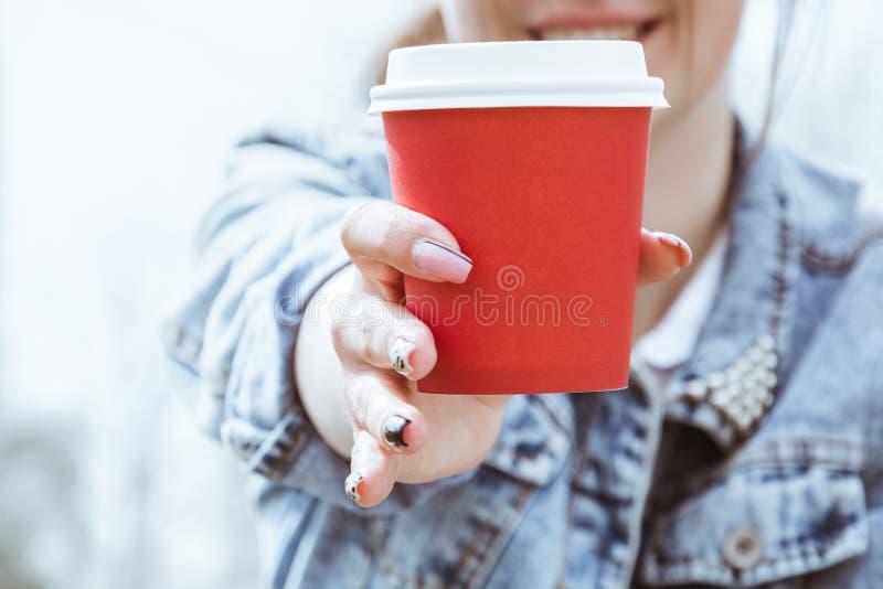 女孩拿着一杯红色纸咖啡 杯咖啡特写镜头在手中 免版税库存照片