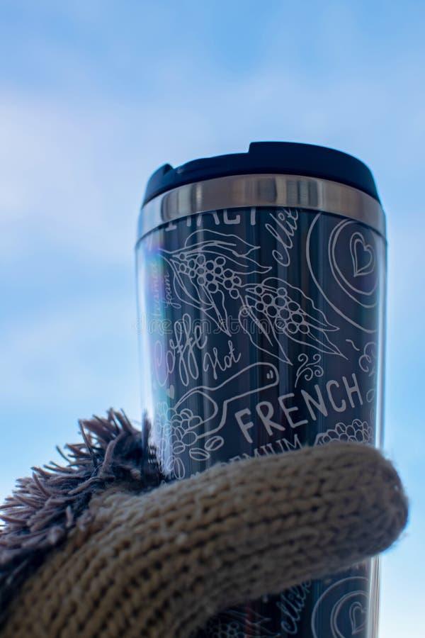 女孩拿着一杯纸咖啡在她的手套的 妇女在冬天享受她热的热奶咖啡饮料 图库摄影