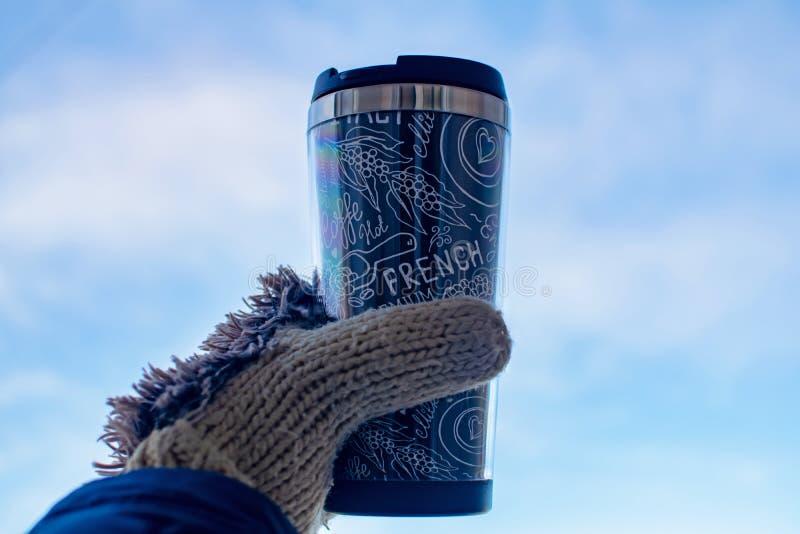 女孩拿着一杯纸咖啡在她的手套的 妇女在冬天享受她热的热奶咖啡饮料 库存图片