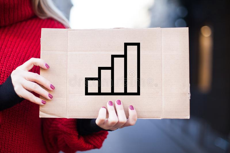 女孩拿着与企业概念的图象的一个标志成功成长过程的 库存照片