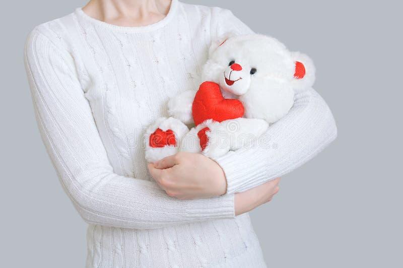 女孩拿着与心脏的一头北极熊在她的手上 灰色背景 免版税库存照片