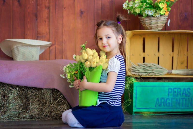 女孩拿着与黄色郁金香的一个篮子 复活节屋子的春天装饰 图库摄影