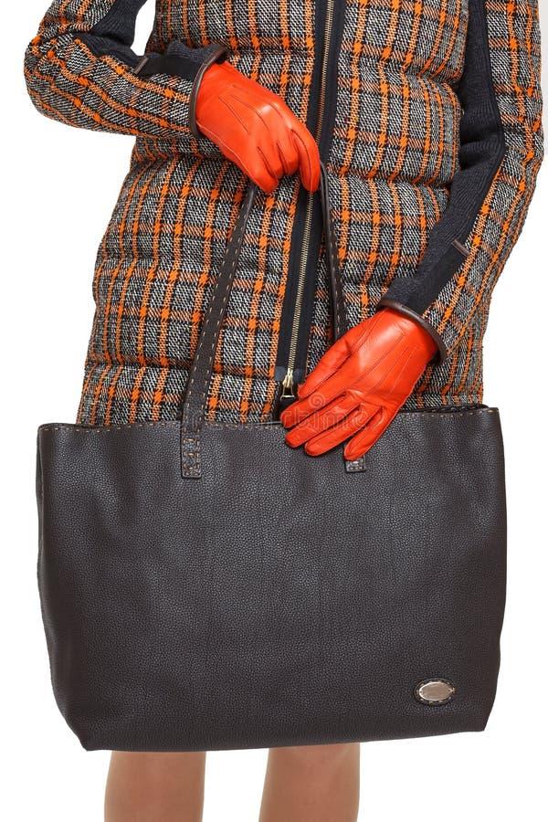 女孩拿着在被隔绝的白色背景的一个棕色袋子特写镜头 免版税图库摄影