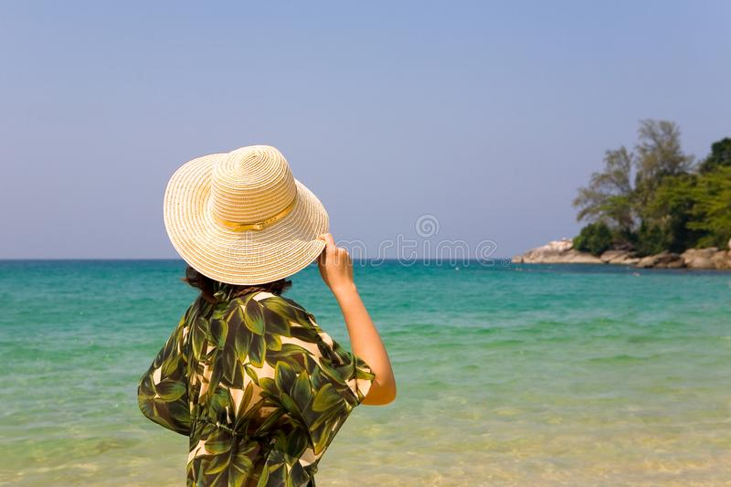 女孩拿着她的帽子并且看海洋 免版税库存照片