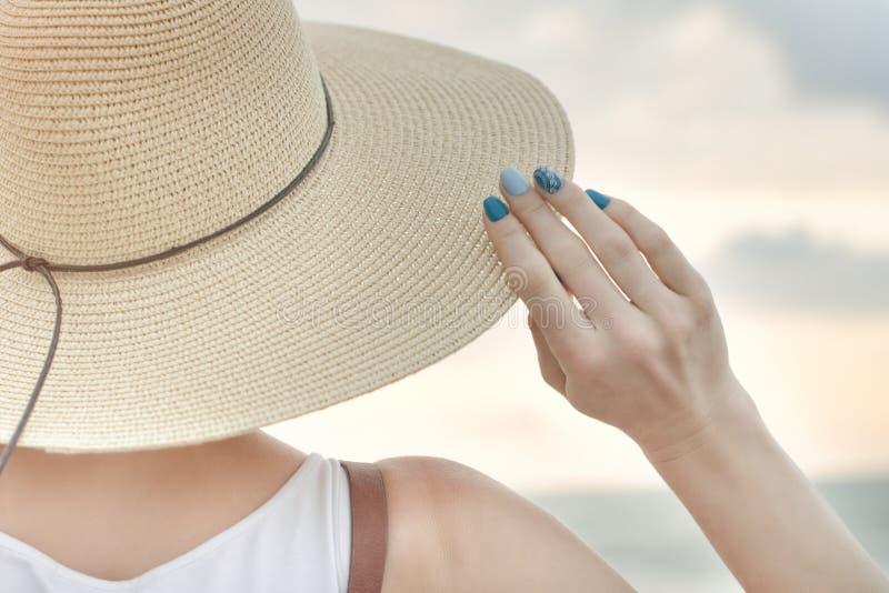 女孩拿着她的帽子用她的手 关闭 回到视图 免版税图库摄影