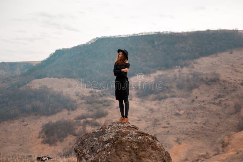 女孩拿着她的帽子,转动她回到谷与山 在岩石的逗留 免版税库存图片