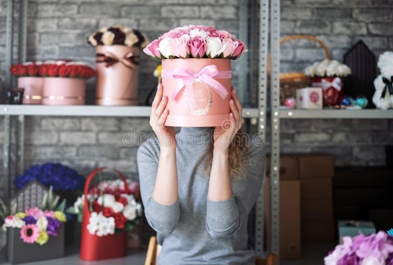 女孩拿着有桃红色玫瑰花束的一个大箱子并且用花束盖面孔 卖花人` s车间 免版税库存照片
