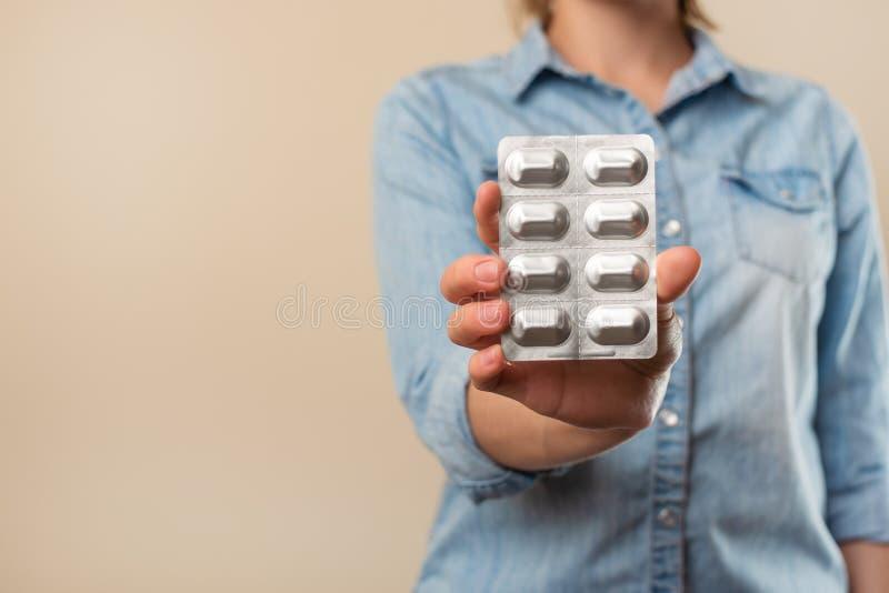 女孩拿着有药片的一块板材在轻的背景,疾病,药房,医学销售,治疗 免版税库存照片