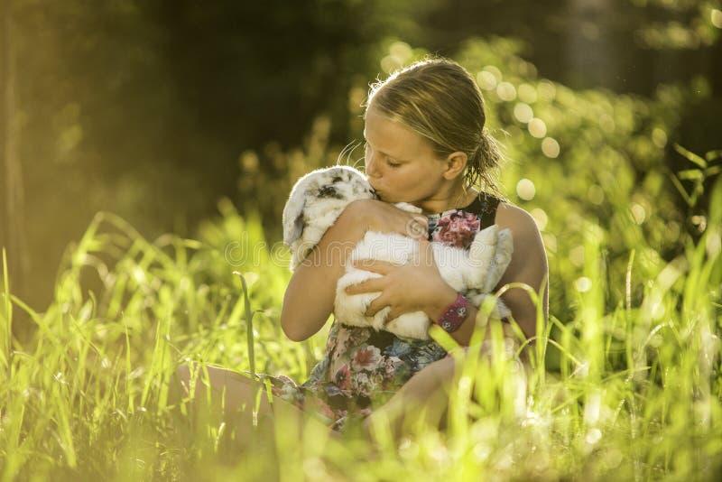 女孩拿着白色兔子 免版税库存照片