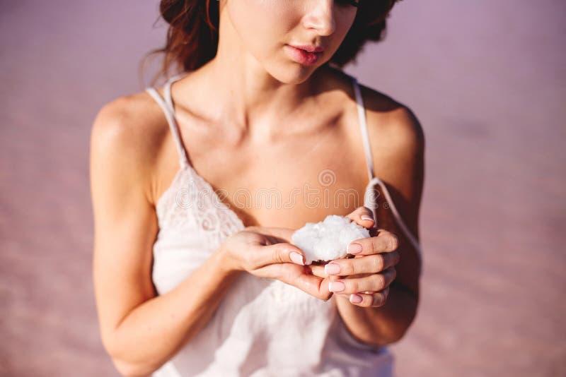 女孩拿着盐水晶 库存照片